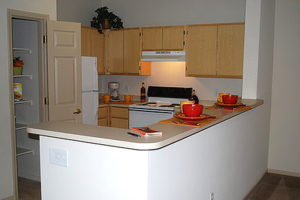 Kitchen with pantry, fridge, oven, and cabinets