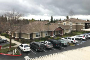 Overview shot of Geneva Pointe's exterior and cars parked in parking lot
