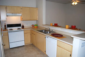 Elk Grove, CA Apartments - Geneva Pointe Kitchen with Wood Style Floor and Breakfast Bar