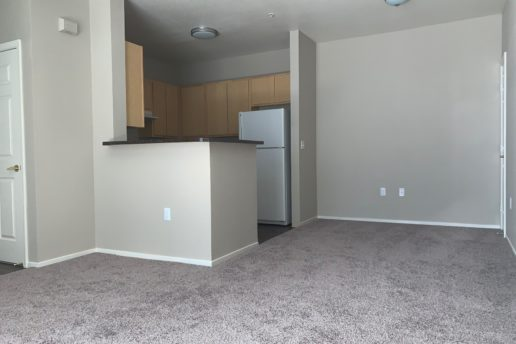 Carpeted dining and living area facing kitchen with island